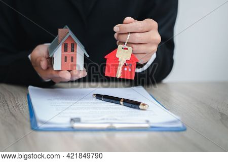 Home Sales Brokers Are Offering Home Sales ,model House On Hand. Real Estate And Residential Concept
