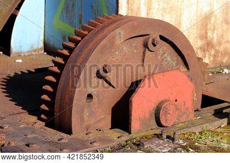 Closeup Of Large Vintage Rusted Old Railway Turntable Or Wheelhouse Cogwheel Mounted On Side Of Rail