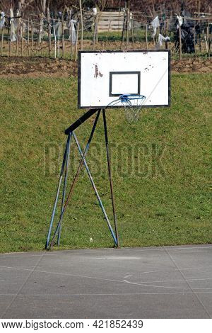 Heavily Used Old Dilapidated Basketball Hoop Mounted On Strong Partially Rusted Metal Frame On Edge