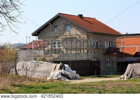 New Suburban Family House Under Construction Surrounded With Building Scaffolding And Other Houses N
