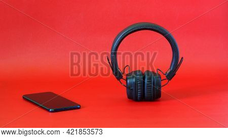 Wireless Headphones With Ear Pads Next To A Smartphone On A Red Background. The Concept Of Listening