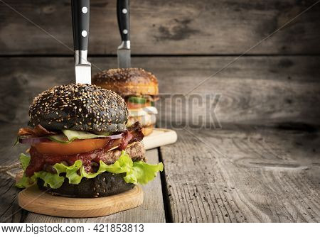 Cheeseburger With Black Bun, Meat And Vegetables On A Wooden Background, Fast Food And Knife, Copy S