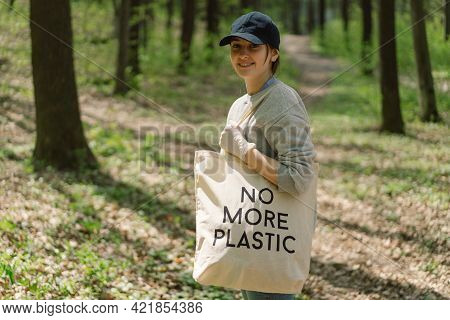Volunteer Woman Is Cleansed In The Forest. Woman Collects Plastic. Woman Volunteer With A Bag With T