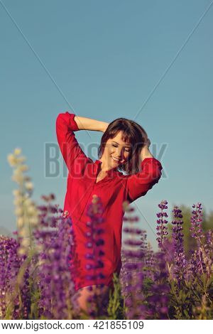 Young Brunette Woman Stands In Red Shirt In Field Of Purple Lupins On Sunset, Copy Space