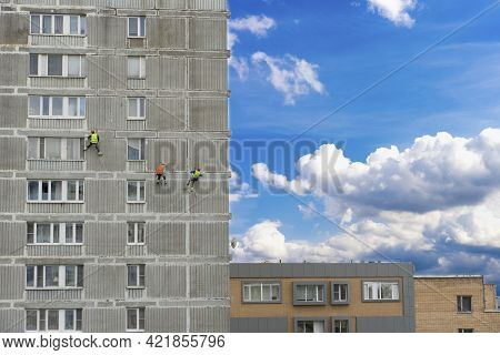 Working At Altitude, Industrial Mountaineering. Three Men Examine The Wall Of A Residential Building