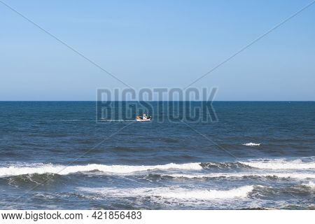 A Small Fishing Boat Sailing Far Away In The Open Atlantic Ocean Seen From The Shore Of Quiaios Beac