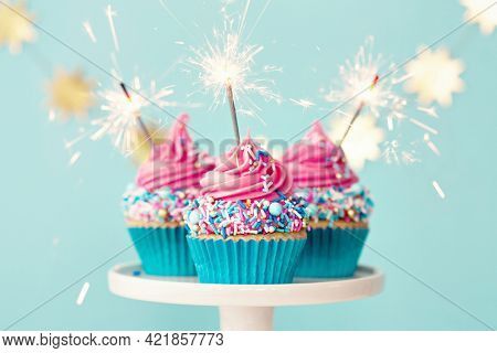 Three birthday cupcakes with pink frosting and party sparklers