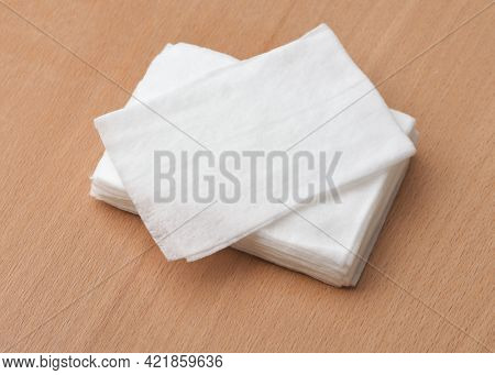 Closeup of unwrapped wet wipes stack on wooden table