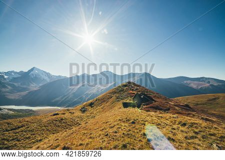 Scenic Autumn Landscape With Sharp Shattered Stone On Red Hill On Background Of Snowy Mountains Silh