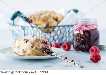 Raspberry Scone With A Jar Of Raspberry Jam And A Basket Of Scones In Behind.