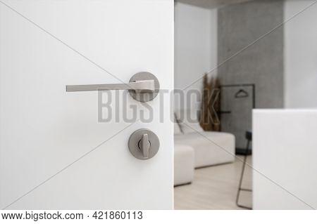 Closeup Of Open White Door With Simple Steel Matt Doorhandle And Lock, Blurred View Of Room With Whi