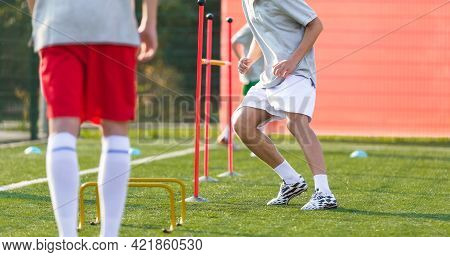 Teenage Football Players On Training Camp. Young Boys Running Slalom Track Between Training Poles An
