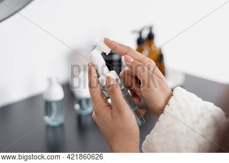 Cropped Shot Of Woman Touching White Face Silicone Brush With Transparent Bottle Before Using It For