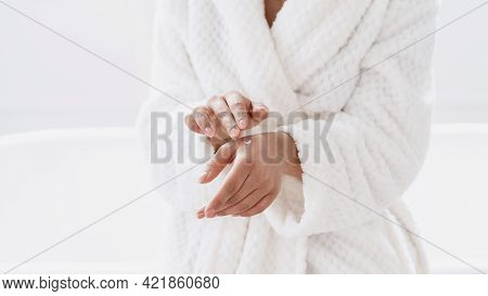 Cropped Shot Of Young Woman Applying White Moisturizing Cream On Her Hand As Part Of Everyday Skinca