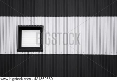 Black And White Corrugated Iron Sheet Used As A Facade Of A Warehouse Or Factory With A Window. Text