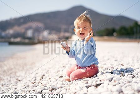 Laughing Kid Sits With A Pebble In One Hand And A Raised Second Hand On A Pebble Beach Against A Bac
