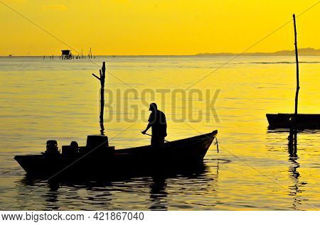 Silhouette Of Traditional Fisherman With The Fishing Boat Going To Fishing During Golden Sunrise In