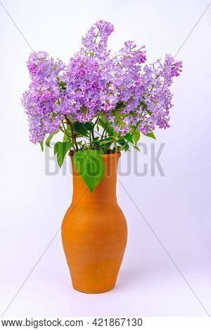 A Tall Brown Earthenware Vase With A Bouquet Of Blooming Lilacs And Green Leaves Stands On A Table C