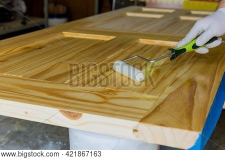 Worker Hand In Glove Varnished Wood Door For Lacquering Using Hand Roller Of Repairman Painting