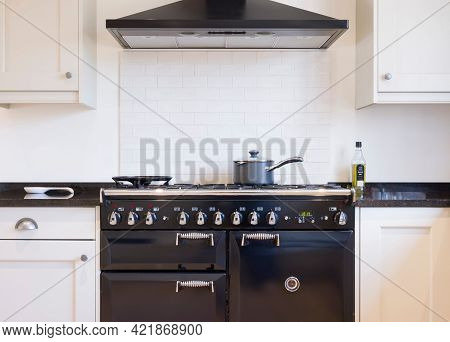 Black And White Kitchen Design. Painted Wood Modern Kitchen With Black Enamel Range Cooker And Chimn
