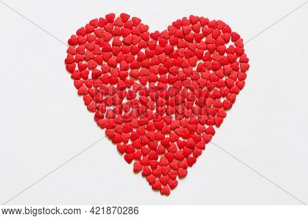 Heart Of Red Hearts Candy On White Surface Close Up. Valentines Day Concept. Macro. Sweet Red Candy
