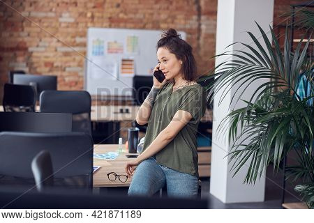 Young Woman, Architect Or Interior Designer Looking Away While Talking On The Phone, Standing In Mod