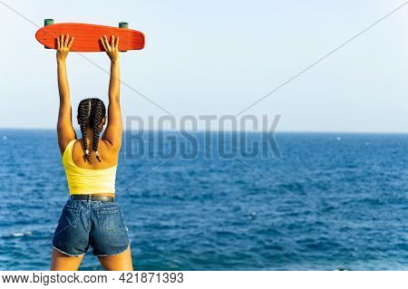 Girl Looking Far Away On The Beach.  Copy Space Of Teen With Skateboard Looking View Of Beach Backgr
