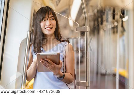 Young Asian Woman Passenger Using Social Network Via Technology Tablet In Subway Train When Travelin
