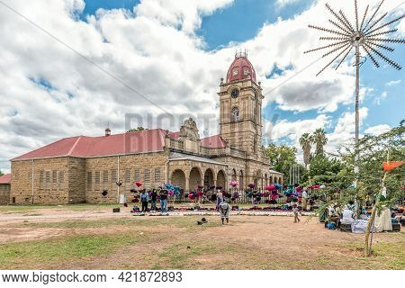 Oudtshoorn, South Africa - April 5, 2021: Vendors With Their Goods, Dusters Made From Ostrich Feathe