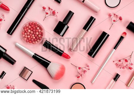 Various Cosmetic Accessories For Makeup And Manicure On Trendy Pastel Pink Background With Red Flowe