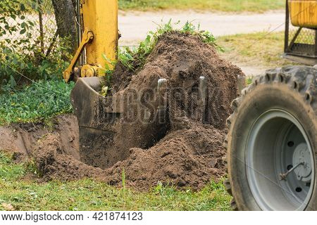 A Bucket Of A Bulldozer Digs The Ground With A Grass Close-up In An Industrial Area. Excavation Work