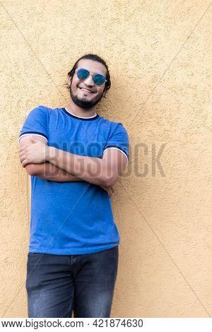 Young Latino Man Wearing Sunglasses And Casual Clothes Standing On Yellow Wall Smiling Confidently W