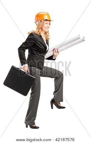 Full length portrait of a mature female architect with helmet holding blueprints and suitcase, walking with big steps isolated on white background