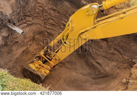 The Hydraulic Piston Of The Excavator Bucket With The Ground Digs A Hole On The Construction Site Cl