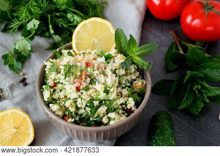 Traditional Oriental Salad Tabouleh With Couscous Or Bulgur On Adark Concrete Background. Ingredient