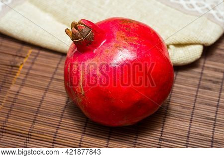 Large Fresh Fruit Of Pomegranate With A Woven Napkin On A Bamboo Mat, Still Life, Close-up