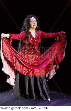 Gypsy Woman Barefoot With Long Black Hair Dances Waving Red-black Skirt On A Black Background. Verti