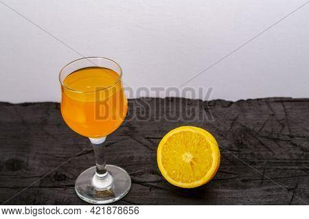 Orange Juice In A Glass Near Oranges On A Black Background. Horizontal Photo