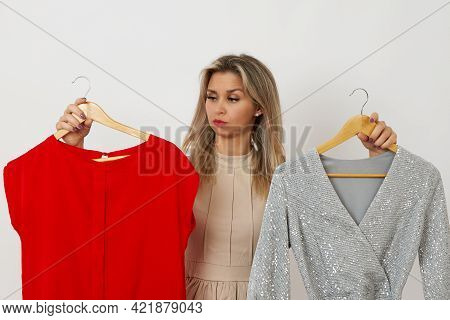 A Pretty Woman Can Not Choose A Dress On A White Background Which Dress To Choose Silver Or Red
