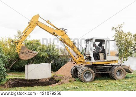 Hydraulic Piston System Of The Excavator With A Bucket, Lowering Into The Pit On Steel Cables Concre