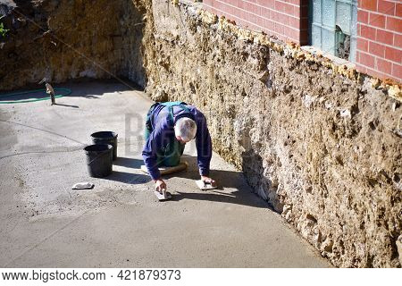 The Mason Kneels And Cleans The Concrete Floor