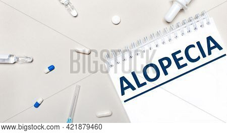 On A Light Background, A Syringe, A Stethoscope, Vials Of Medicine, An Ampoule And A White Notepad W