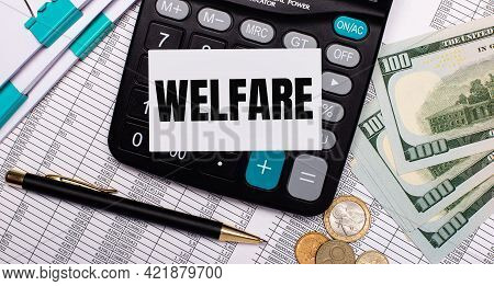 On The Desktop Are Reports, A Pen, Cash, A Calculator And A Card With The Text Welfare. Business Con