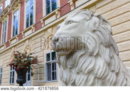 Lancut, Poland - August 26, 2020: Statue Of Stone Lion In Front Of 16th Century Baroque Lancut Castl