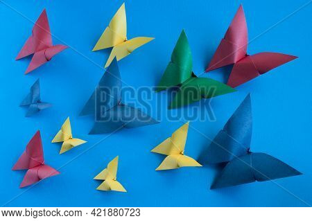 Multicolored Origami Paper Butterflies Of Different Sizes On A Blue Paper Background