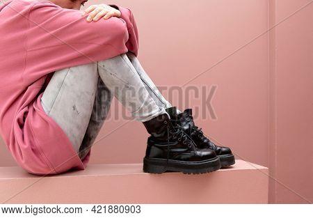 Sitting woman wearing combat boots