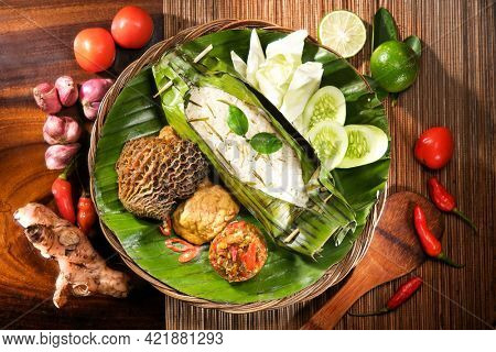Indonesian Nasi Bakar Babat, Grilled Aromatic Rice wrapped in Banana Leaves with Beef Tripe and Fresh Salad