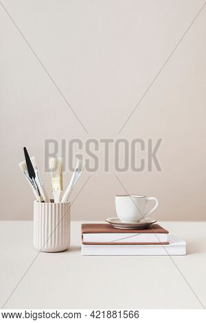 Paintbrushes and cup on top of books