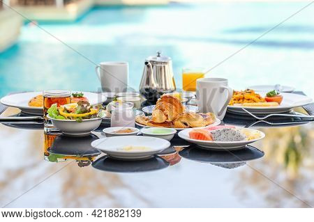 American Breakfast Set With Teapot On Table Next To Poolside In Resort. English Morning Food Near Sw
