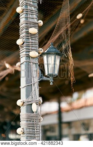 Lantern Hangs On A Pole Braided With Fishing Tackle Under A Canopy From Which A Fishing Net Hangs